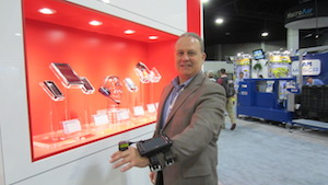 <p> Honeywell's (Booth 4935) Bruce Stubbs, director of supply chain marketing, shows of the company's enhanced D75E wearable computer with ring scanner.</p>