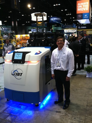 <p>JBT marketing manager Mark Longacre next to a JayBot, JBT's new AGV with on-board intelligence that eliminates the need for a central system manager.</p>