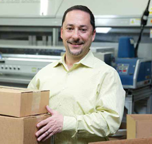 <p>Jerry Imbrenda, fulfillment center manager at the Secaucus facility, with some of the custom-sized boxes from the company's Smart-size Packaging Program.</p>