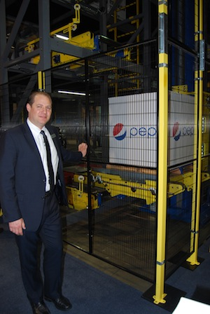 <p>Cory Hypes, executive VP of PAS, stands by as the PowerStor's vertical lift device moves up to 120 pallets per hour.</p>