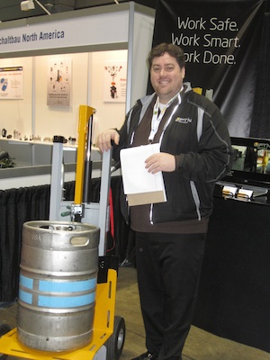 <p>Aaron Lamb, president, shows one of the Lift&#8217;n Buddy&#8217;s newest features&#8212;a cylinder handling attachment that grips drums and kegs.</p>