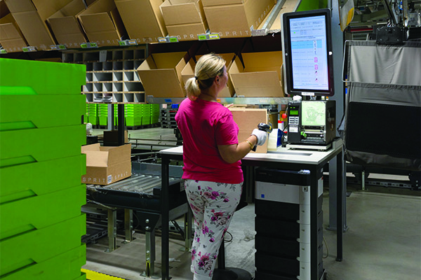 <p>In the packing area, an associate removes items from the pouch sorter and packs them for shipping.</p>