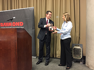 <p>Michael Field, CEO of The Raymond Corp., presents a statue commemorating Raymond&#8217;s 500,000th lift truck to Tara Hamachek, manager of building services operations for the Home Depot.</p>